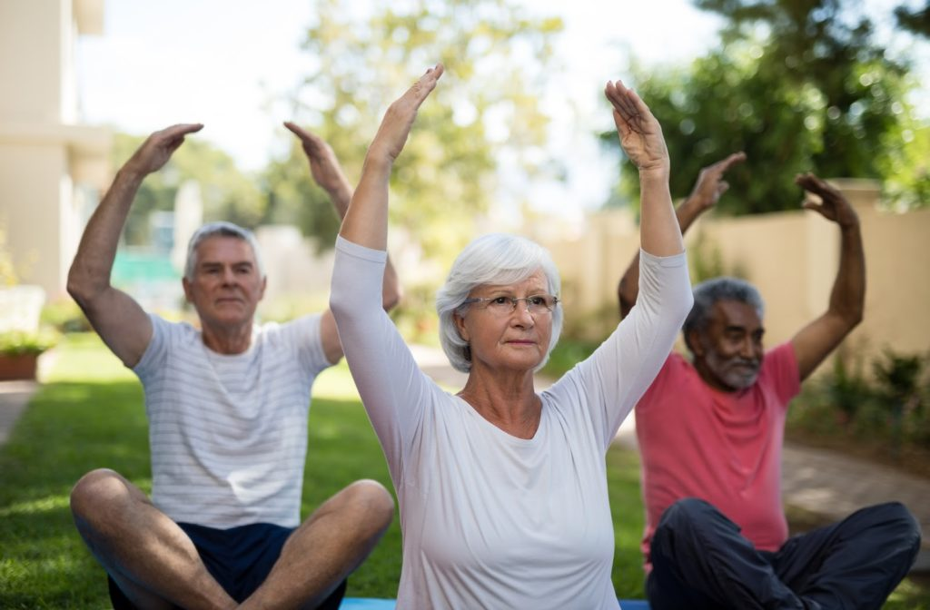 Seniors participating in yoga outside in the communities park.