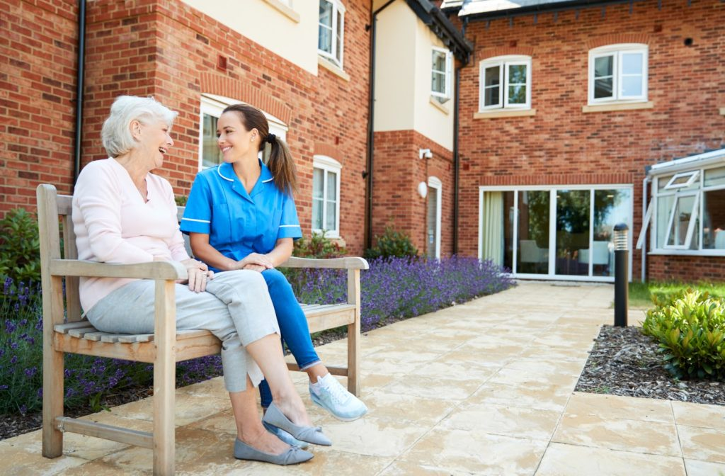 Senior woman accompanied by nurse as they sit on bench outside senior home community